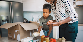 Mom and son organizing groceries on the counter - image