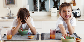Two young children make faces at vegetables in bowls - Image