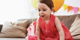 Young girl smiles looking at a cupcake - Hero Image
