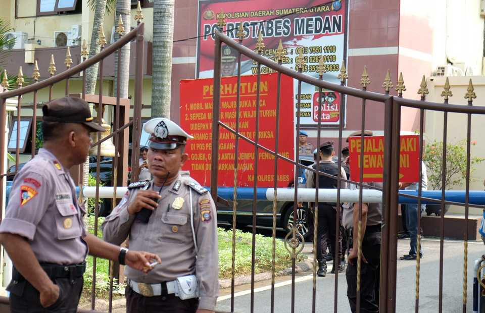 Policemen stand guard at the gate of the Medan Metropolitan Police headquarters in North Sumatra after a suicide bomb attack this morning. (Antara Photo/Irsan Mulyadi)