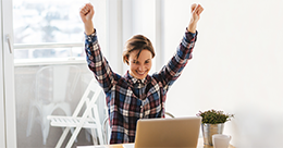 happy woman raises her arms in celebration as she looks at her computer screen