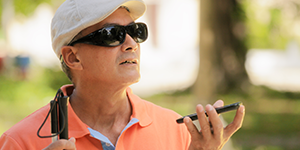 Blind man on a walk, talks to his smartphone