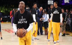 Kobe Bryant holding a basketball with team members in background all wearing �I can't breath� t-shirts on the court.