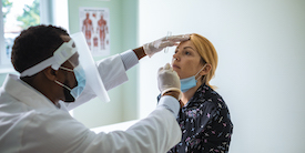 Male doctor swabs the nose of a female patient - Image