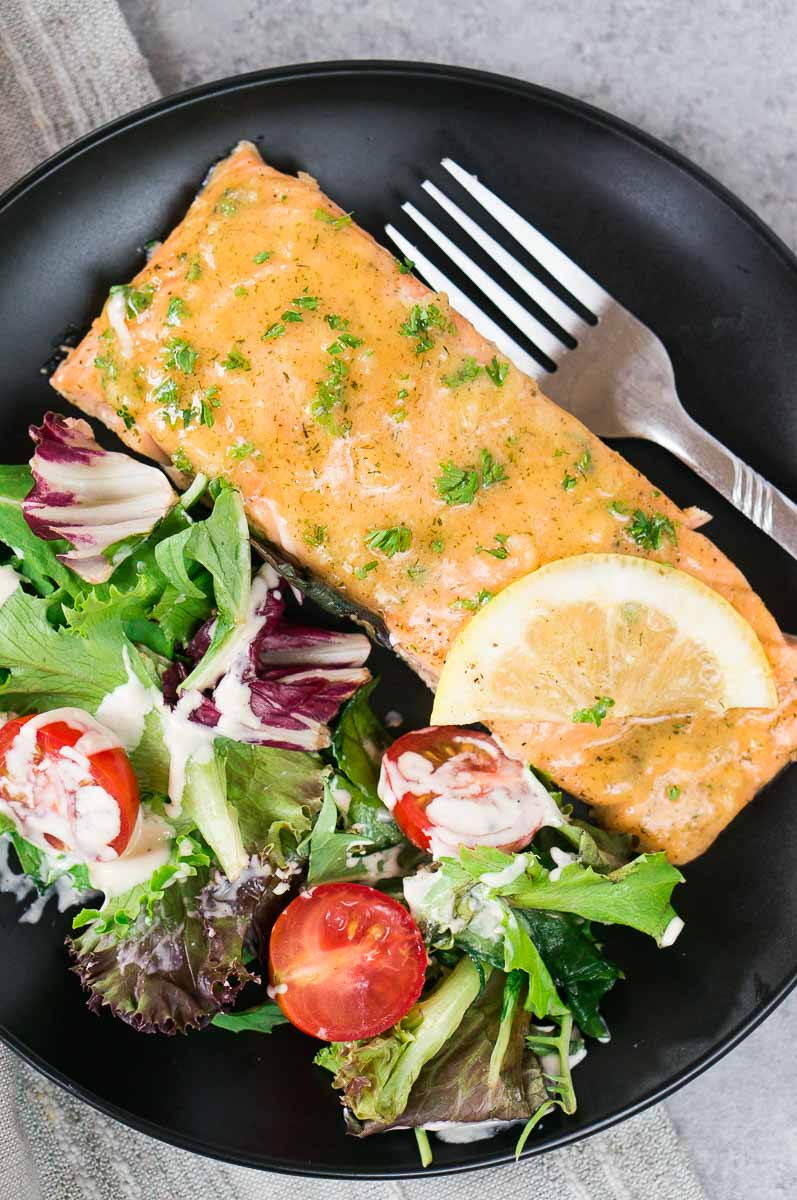 maple mustard salmon on a black plate with green salad