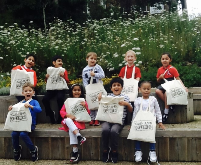 A group of smiling children sit on some steps and hold up cream tote bags