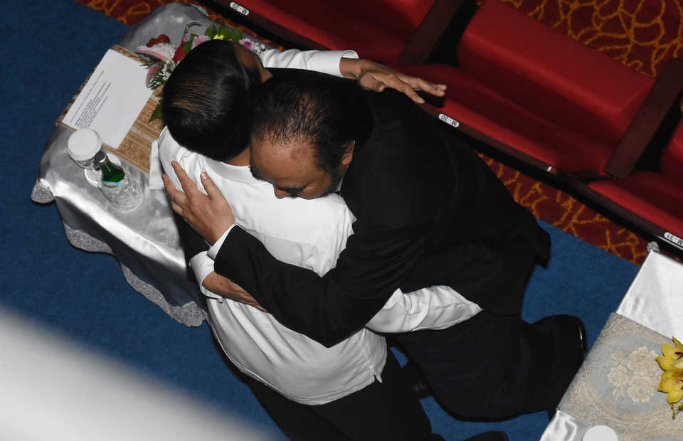 President Joko Widodo, left, is embraced by Nasdem Party Chairman Surya Paloh during the party's congress in Jakarta on Nov. 11, 2019. (Antara Photo/Indrianto Eko Suwarso)