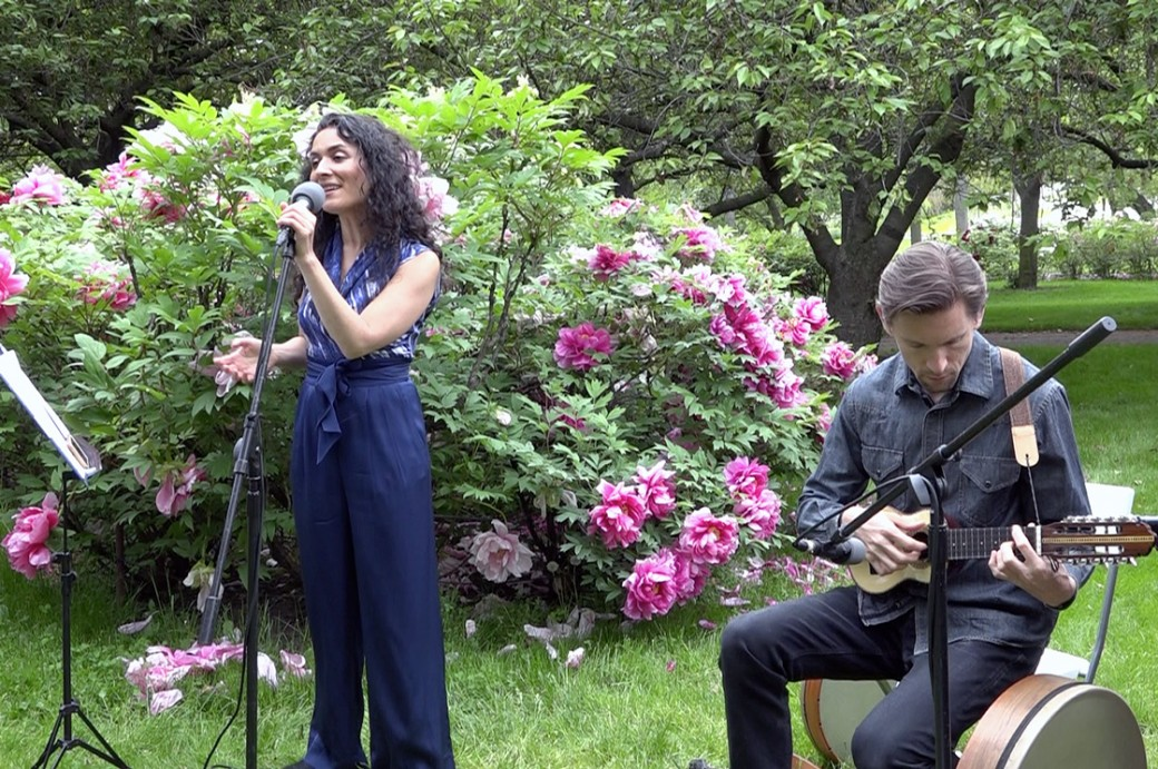 A woman sings in front of a shrub with large flowers, while a man plays guitar.