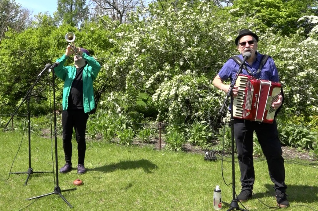 A man with a horn and another with an accordion outdoors on a lawn.