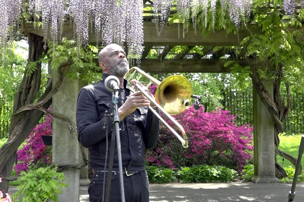 Man with trombone under an arbor of wisteria flowers.