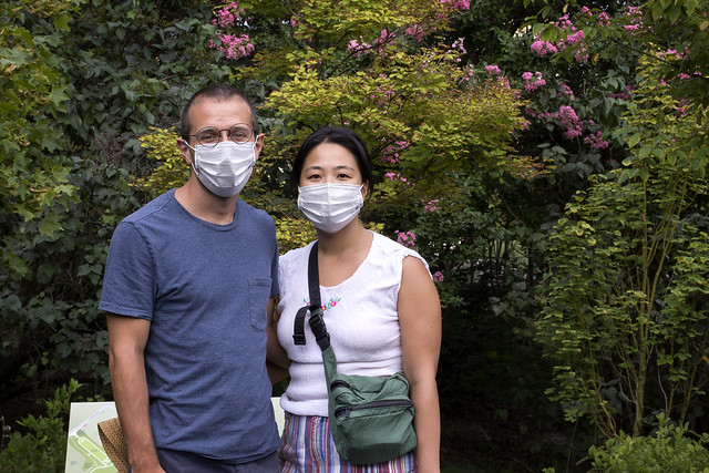 People in face masks in a garden.