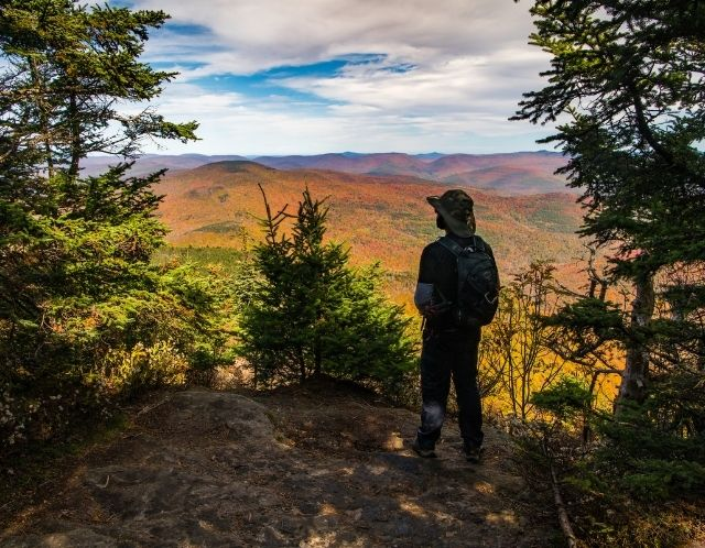 A hiker looks out at foliage from an overlook in the Catskills