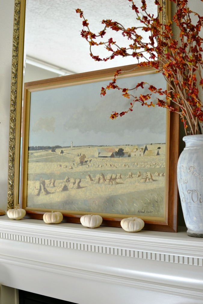 Harvest painting over mantel with pumpkins
