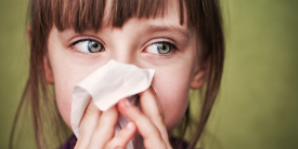 Young girl blows her nose on tissue - image