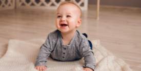 Baby smiling doing tummy time - image