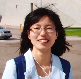 A person wearing glasses and smiling at the camera  Description automatically generated