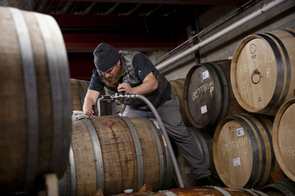 Image of winemaker topping barrels with wine.