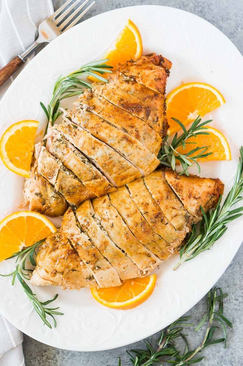 roast turkey breast on a platter with rosemary and oranges