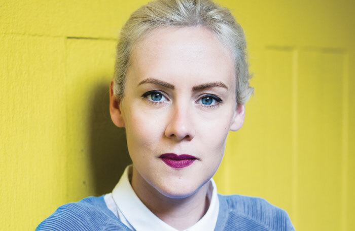 A woman with platinum blone hair in a blue jumper looks directly into the camera, against a yellow background