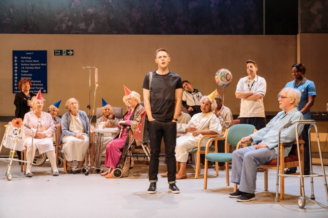 Focus on a young man, standing in the middle of the stage, hands in his pockets. He wears jeans and a T-shirt. He is surrounded by elderly people, sitting in chairs and wheelchairs. In the background, a birthday balloon. Care workers look on.