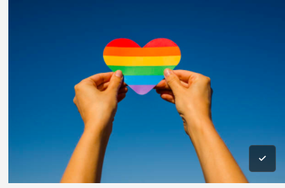 A person holds up a heart-shaped piece of paper with rainbow colors