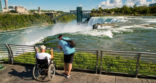 A person in a wheelchair and a companion look out at Niagara Falls.