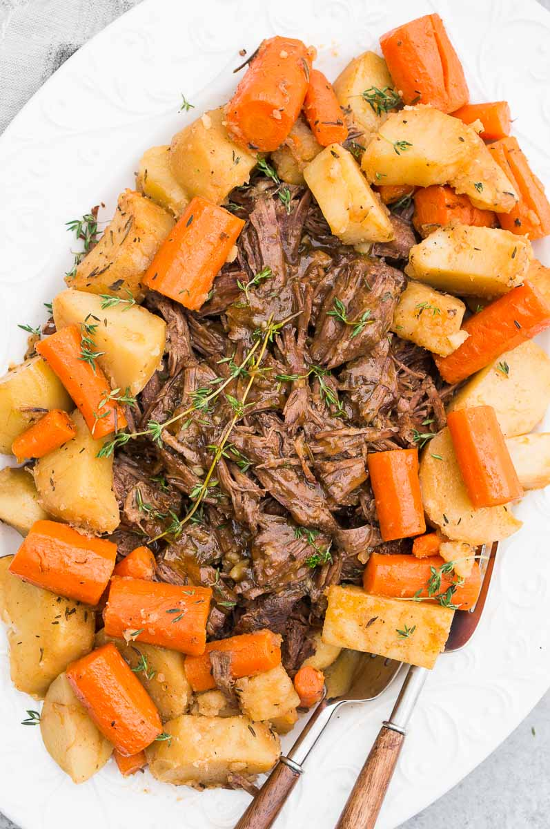 instant pot pot roast with potatoes and carrots served on a white plate