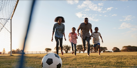 Family playing soccer together outside - image