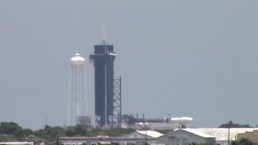 A SpaceX Falcon 9 rocket, seen at right, is lowere