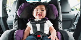 Smiling baby in a carseat - Hero Image