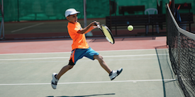 Young boy playing tennis - image