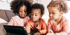 Three adorable toddlers viewing a tablet - Image
