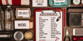 An assortment of labeled hurricane safety items and clipboard on a tan background - image