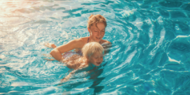 Mother assists her young son in a swimming pool - image