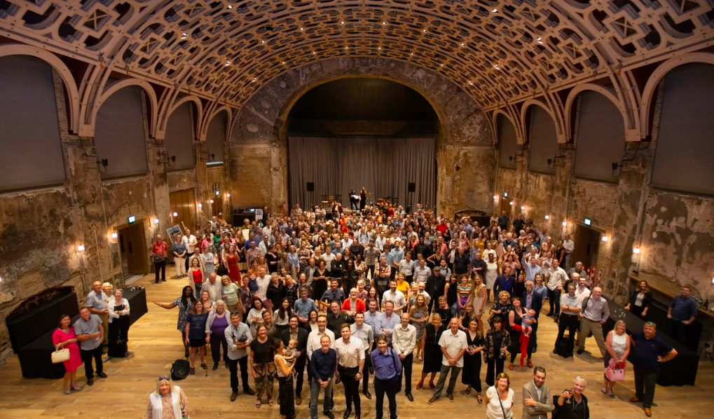 A large group of people in a large hall with a lattice wood ceiling