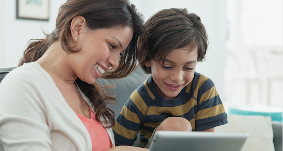 Woman viewing tablet with young son