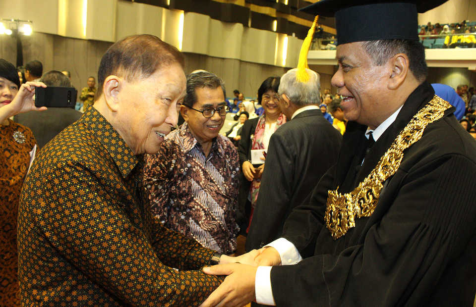 Ari Kuncoro, right, receives congratulations from former chairman of University of Indonesia's Board of Trustees Mochtar Riady after being inaugurated as chancellor in Depok, West Java, on Wednesday. (B1 Photo/Emral Firdiansyah)