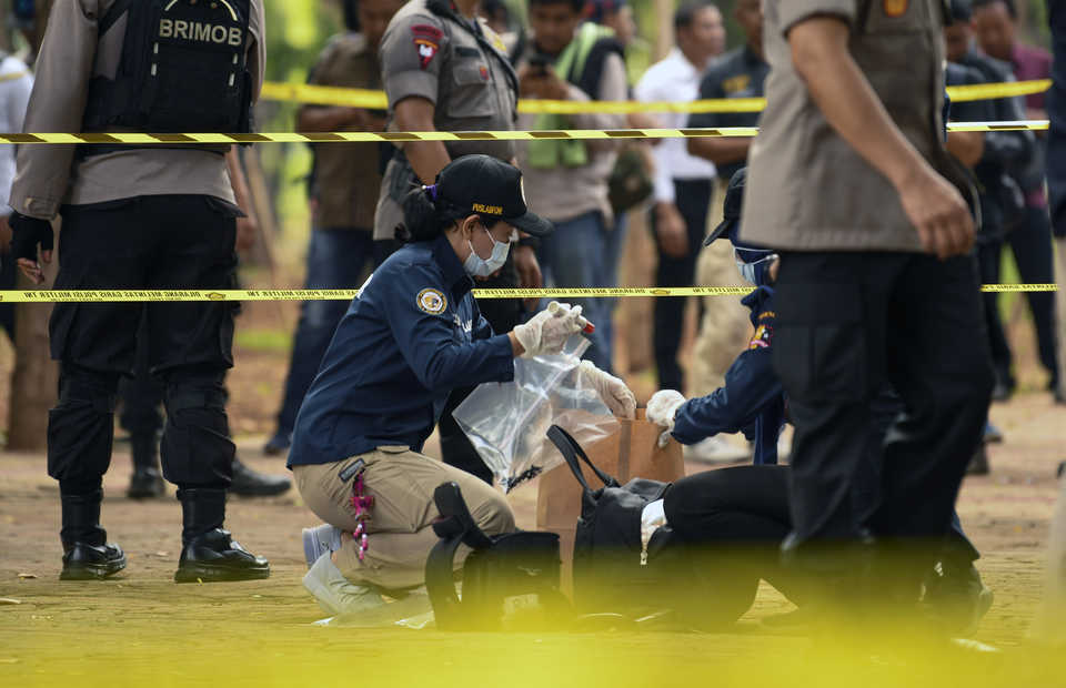The National Police's forensic team collects evidence from the blast site at the National Monument in Central Jakarta on Tuesday morning. (Antara Photo/Nova Wahyudi)