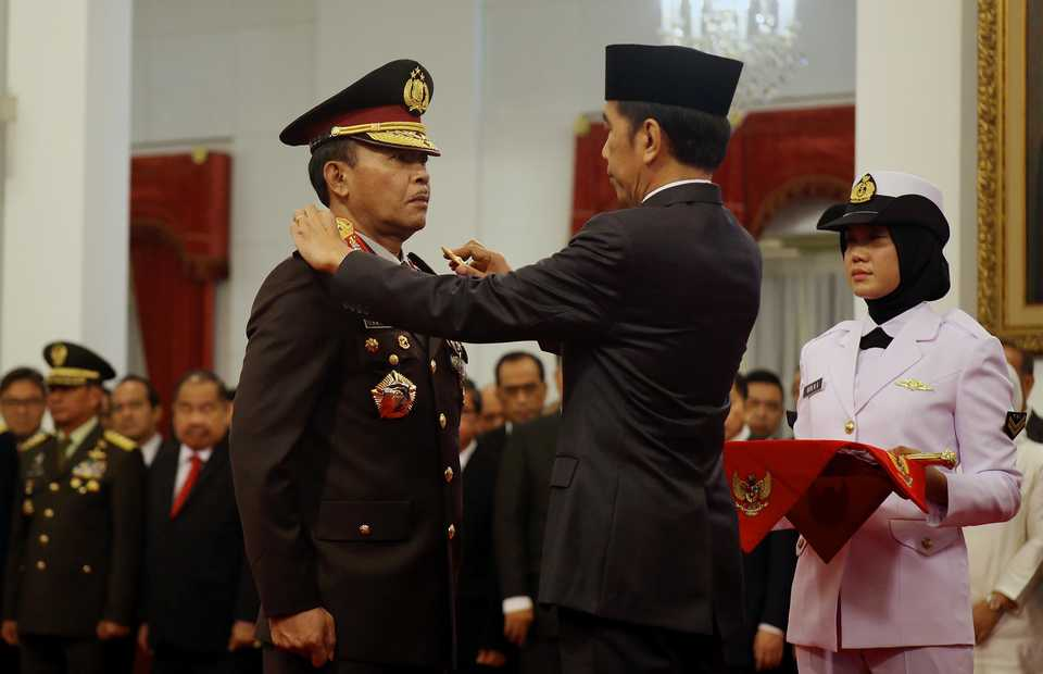 President Joko Widodo swears in Idham Azis as National Police chief by putting on a four-star epaulette on the general during a ceremony at the State Palace in Jakarta on Friday. (B1 Photo/Joanito de Saojoao)