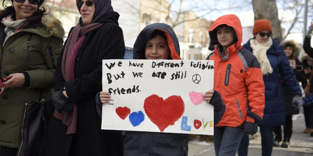 A boy holding a sign that says We have different religion but we are still friends