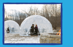Couple dining in a dome with a firepit nearby.