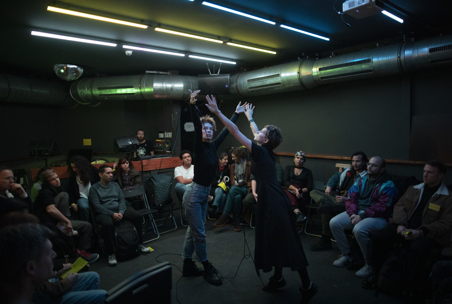 two artists perform in a dark room with audience surrounded