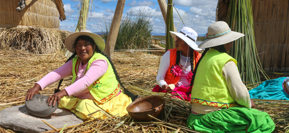 Uru women in colourful traditional attire on floating island of Uros
