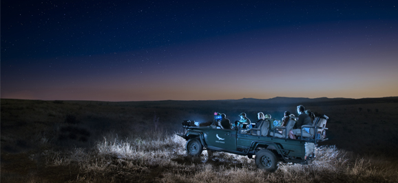 Guests on safari vehicle under the stars watching Night Eye infra-red monitors