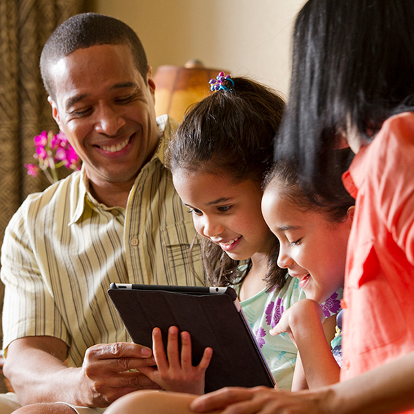 A family of four is gathered around a tablet to make their Theme Park reservations using Disney Park Pass service.