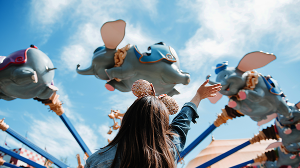 A little girl in rose gold Minnie ears waves as the precious pachyderms of the DUMBO THE FLYING ELEPHANT attraction soar by.