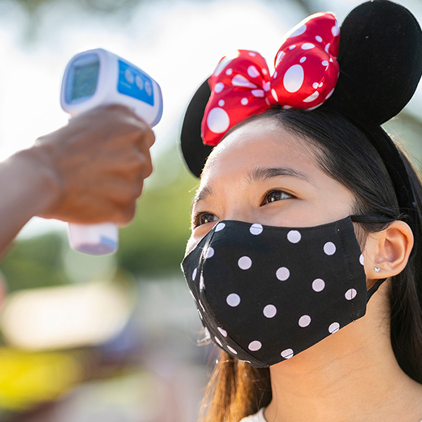 A girl wearing a polka dot face covering and polka dot Minnie Ears gets a touch-free temperature screening.