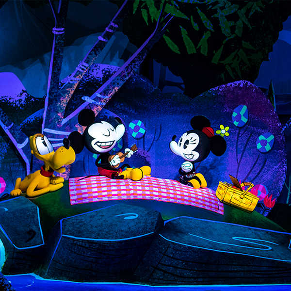 Mickey Mouse plays guitar during a picnic with Minnie and Pluto as part of the Mickey & Minnie's Runaway Railway attraction.