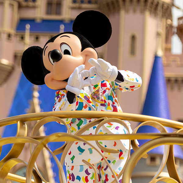 Mickey Mouse in his colorful confetti suit dances on a float as part of his Character Cavalcade at MAGIC KINGDOM Park.