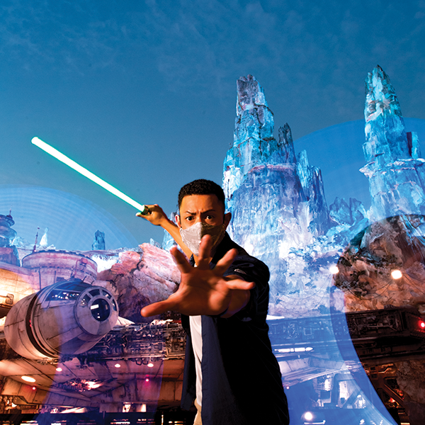 A man wearing a face mask wields a lightsaber in front of the MILLENNIUM FALCON  in STAR WARS: Galaxy's Edge at dusk.